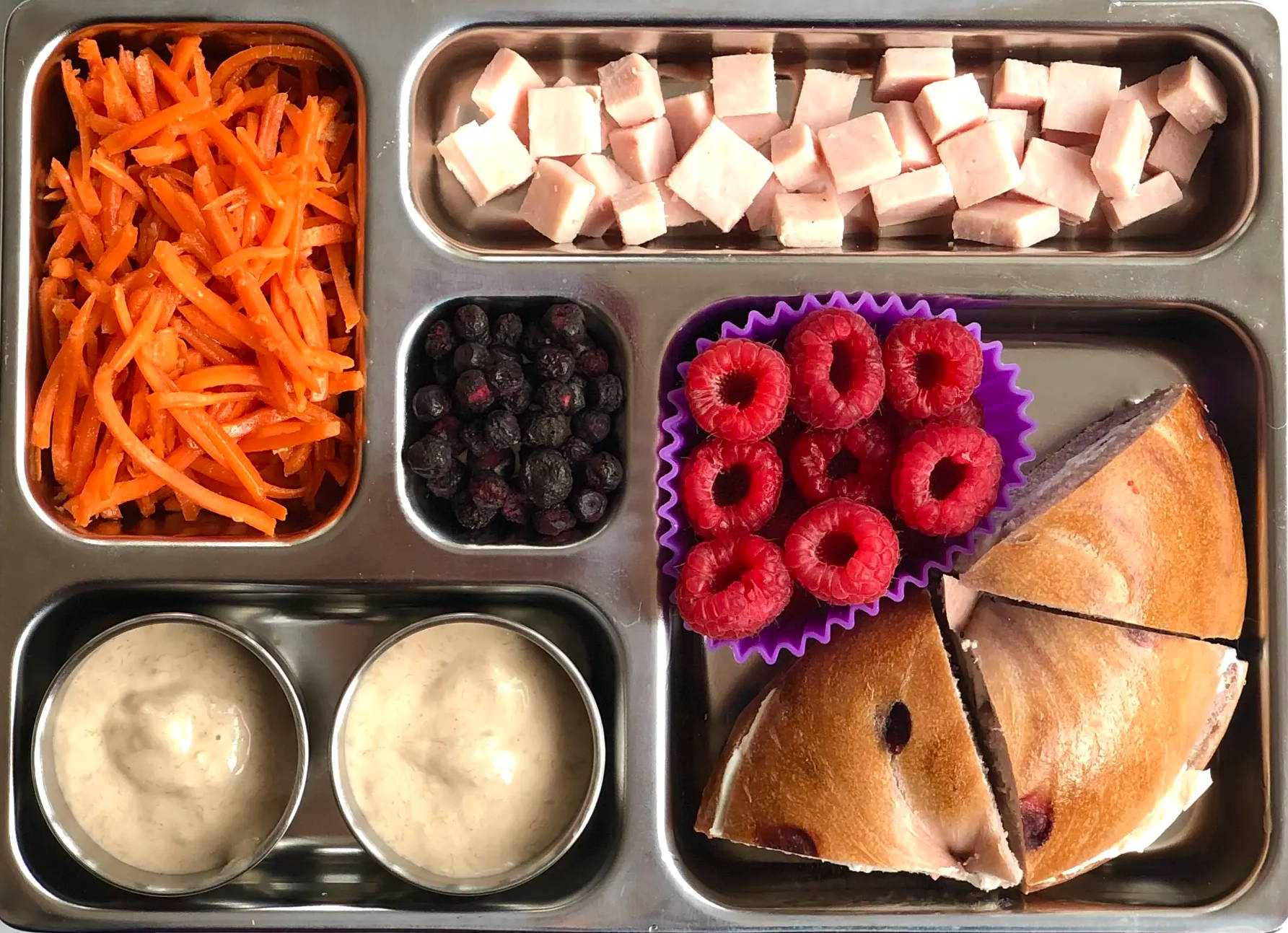 Sneak peek of a kid's quick and healthy school lunch containing Blueberry Bagel with Neufchatel, Carrot-Ginger Slaw, Natural Maple Deli Turkey Cubes, Banana Yogurt, Raspberries, and Freeze-Dried Blueberries..