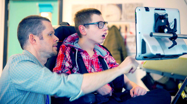 Teenager und sein Lehrer benutzen ein Augensteuerungsgerät der I-Serie+ von Tobii Dynavox, um zu kommunizieren