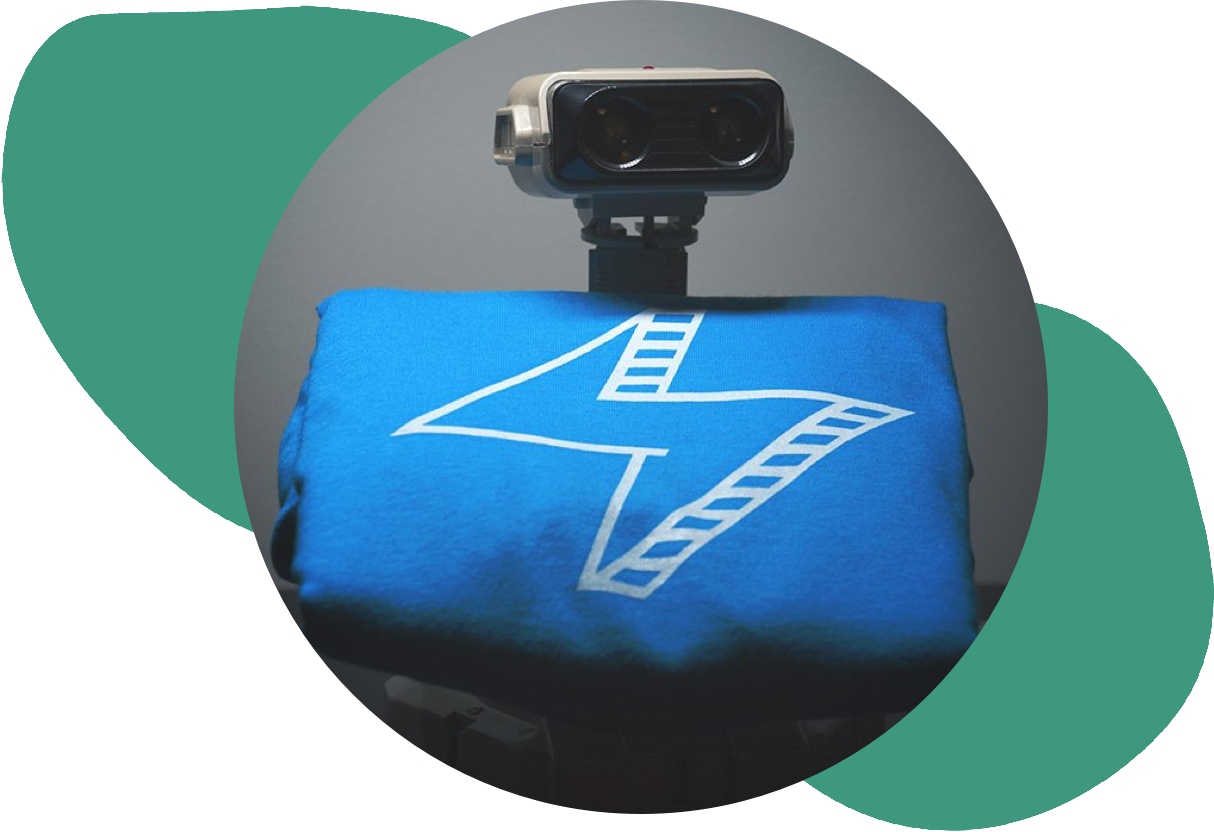 photo of robot holding a folded up blue tshirt with white lightening bolt over an abstract green background