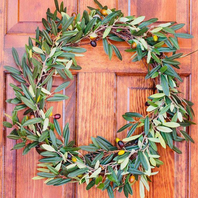 An artificial olive wreath from Nearly Natural decorated on an entrance door