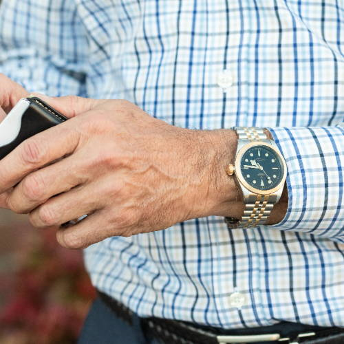 Man wearings a watch and looking through his wallet