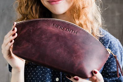 woman holding personalized handmade leather make up that is a great gift for bridesmaids