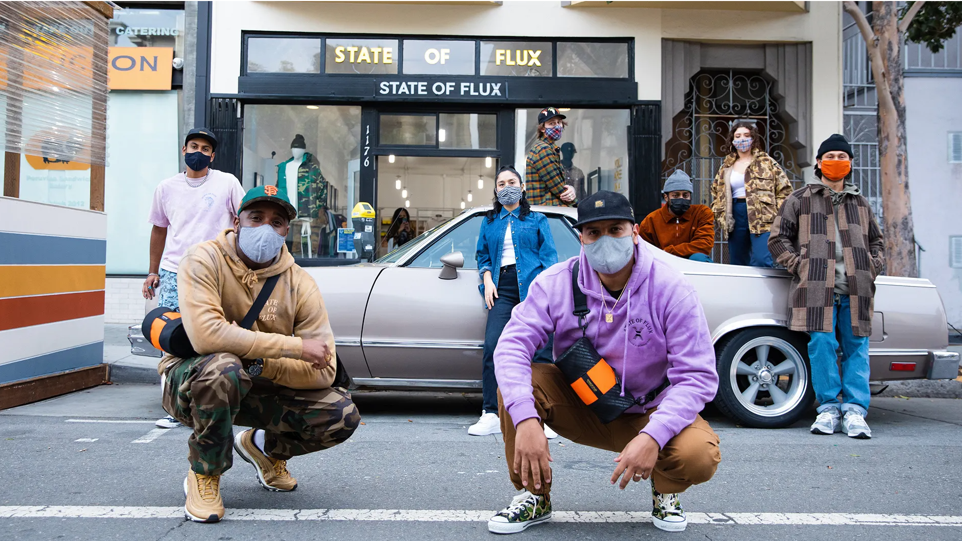 Image of multiple people standing in front of a car and the State of Flux store. Everyone is wearing masks, and some are crouched. Two people in the front are wearing the Mini Hustle Duffel State of Flux Collaboration.