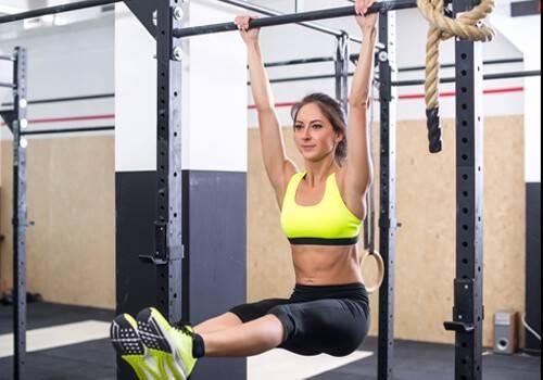 Frau bei der Bauchübung Hängendes Beinheben mit gestreckten Beinen