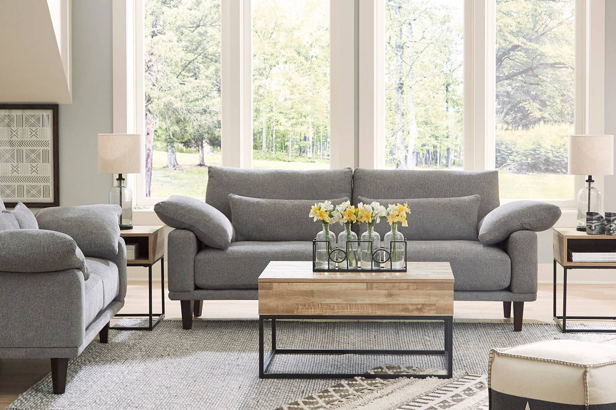 Sunlit living room with comfortable grey sofa and wood table.
