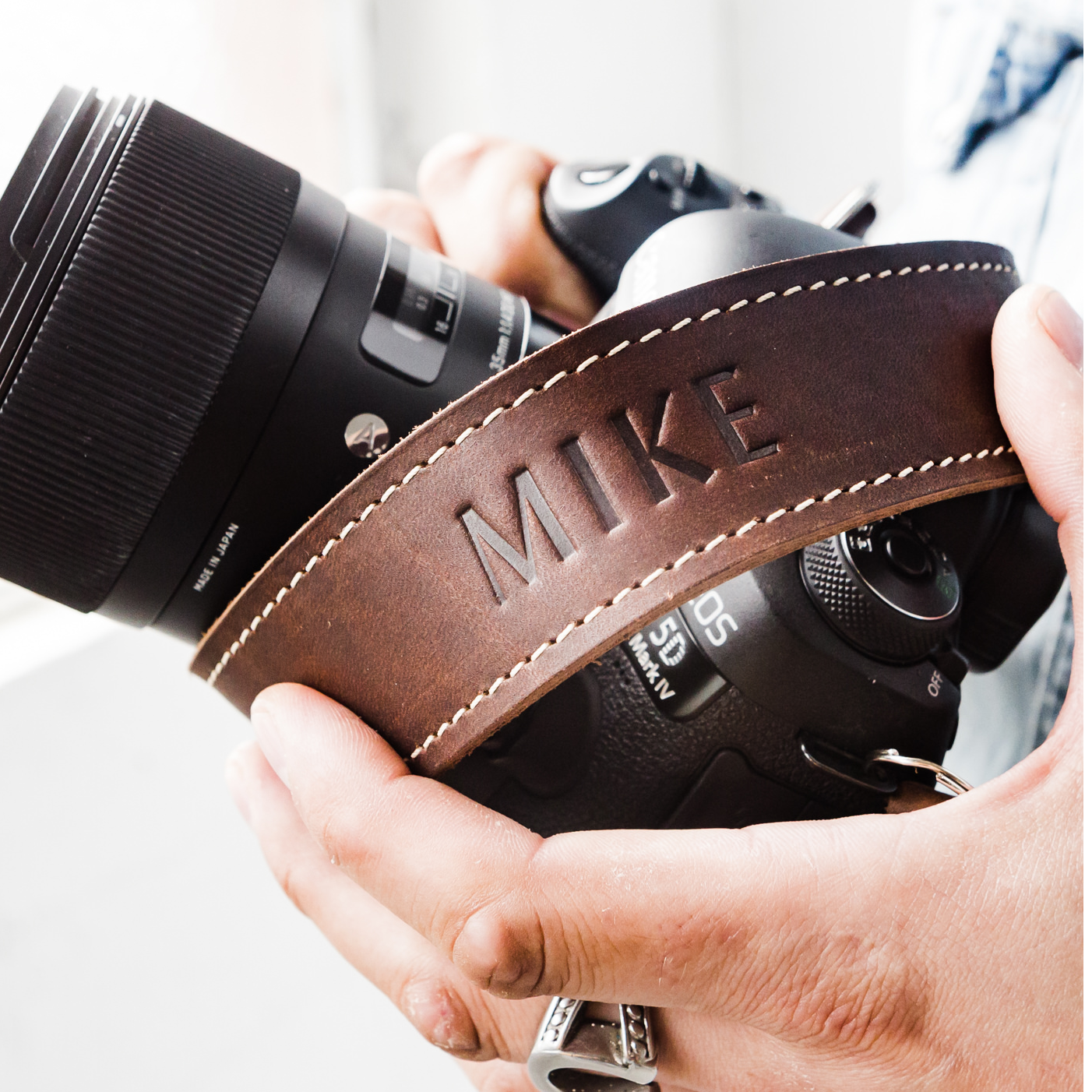 a camera wrapped in a personalized handmade leather camera strap