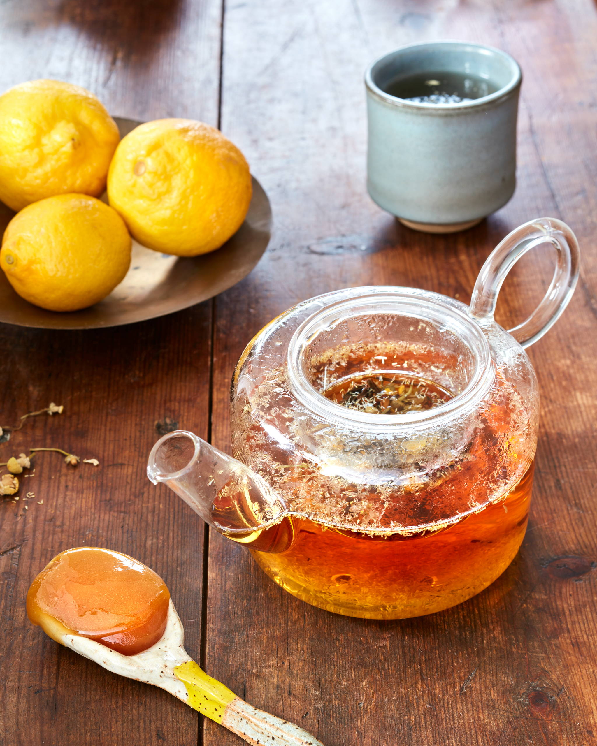 Plate of lemons and glass tea kettle filled with a healthy tea made with manuka honey