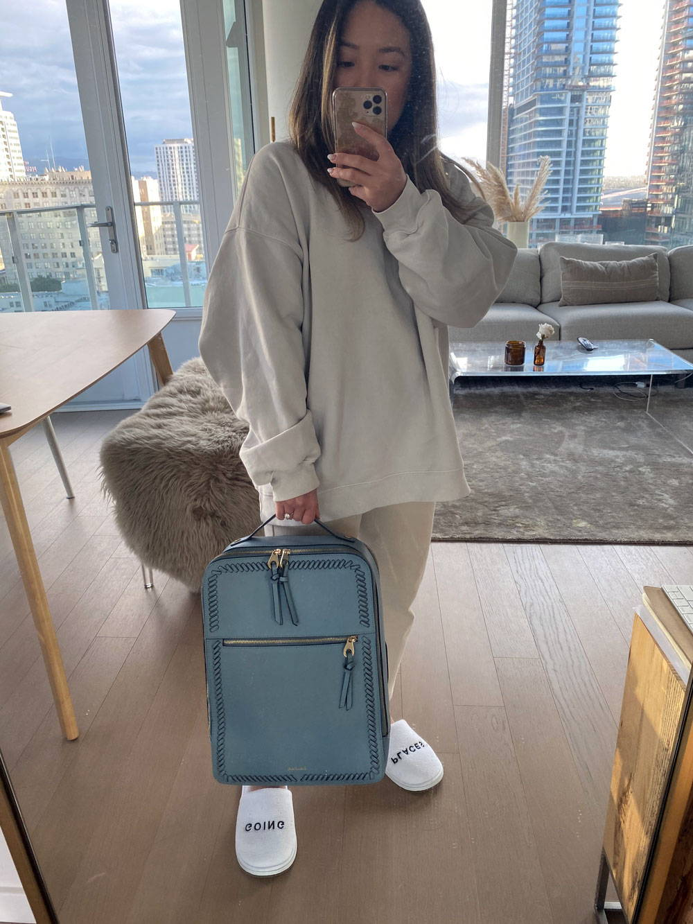 Director of marketing, Jeannie, with CALPAK Kaya Laptop Backpack in Bluebell and Going Places Slippers.