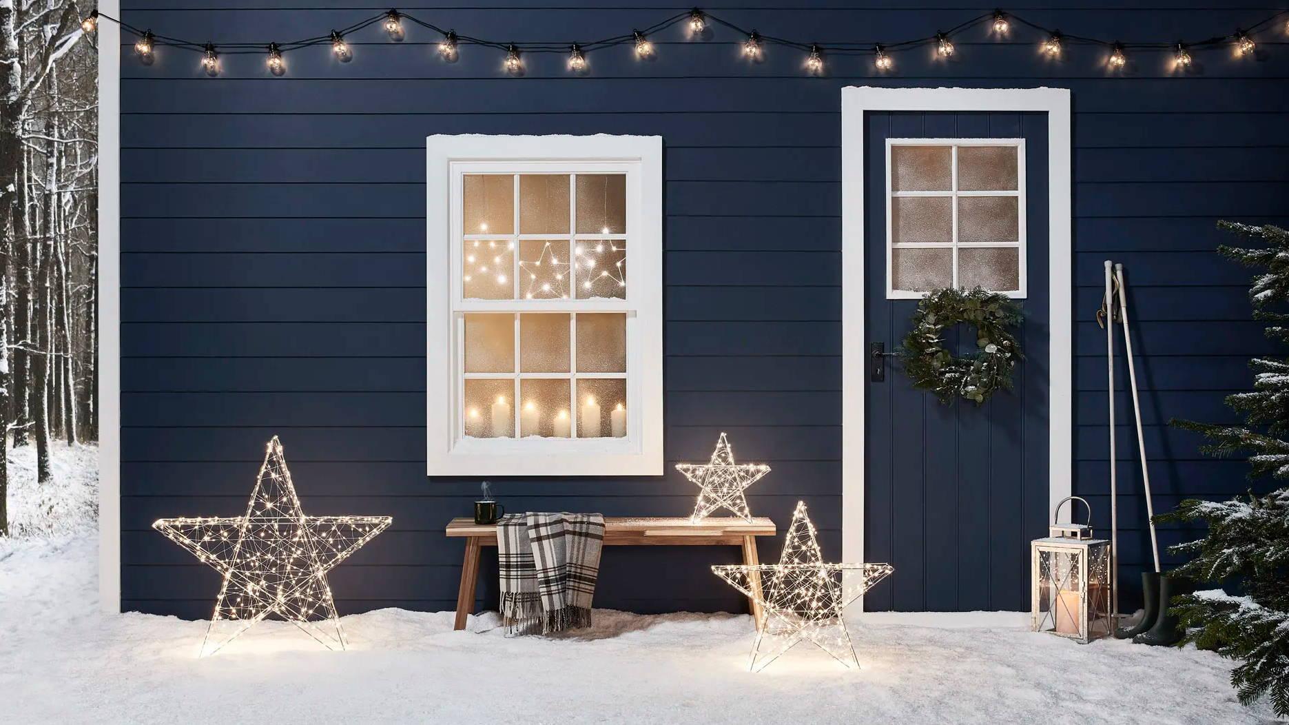 Häuserfassade blau mit Schnee und LED-Stern-Deko .