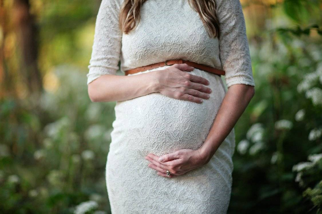 Pregnant Woman In White Dress Holding Stomach With Both Hands