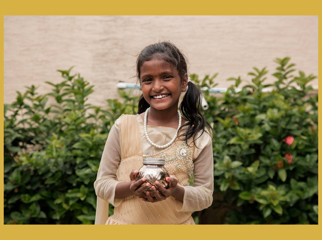 A young Indian Girl in traditional clothing holds a Sweet Grace collection Candle and smiles