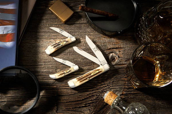 Vintage Bone Trapper, Pocket Hunter, and Swayback knives shown with whiskey, cigar, and book on desk.