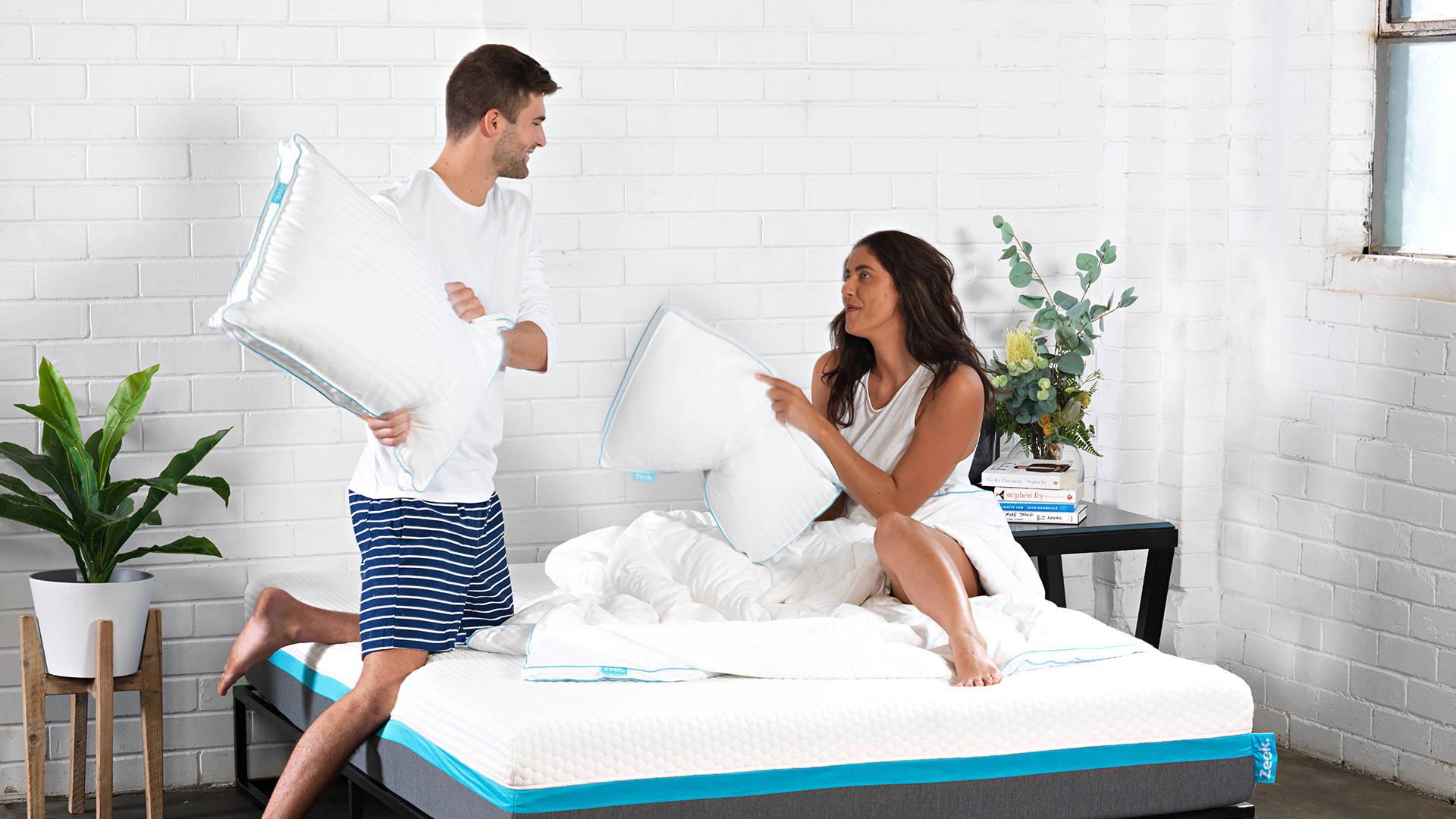 Man and woman having pillow fight with Zeek pillows on Zeek mattress