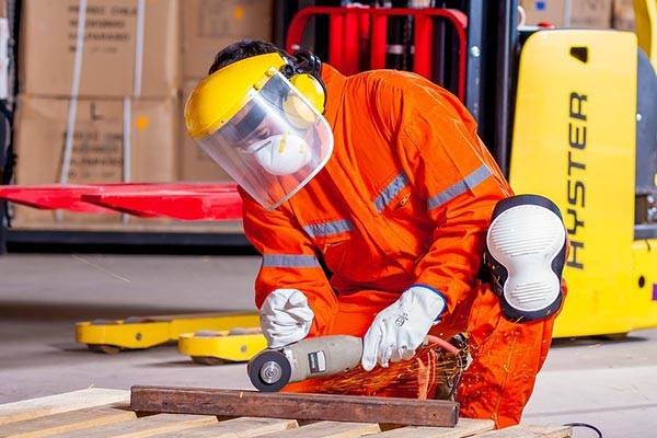 A Man With A Respirator Uses A Grinder