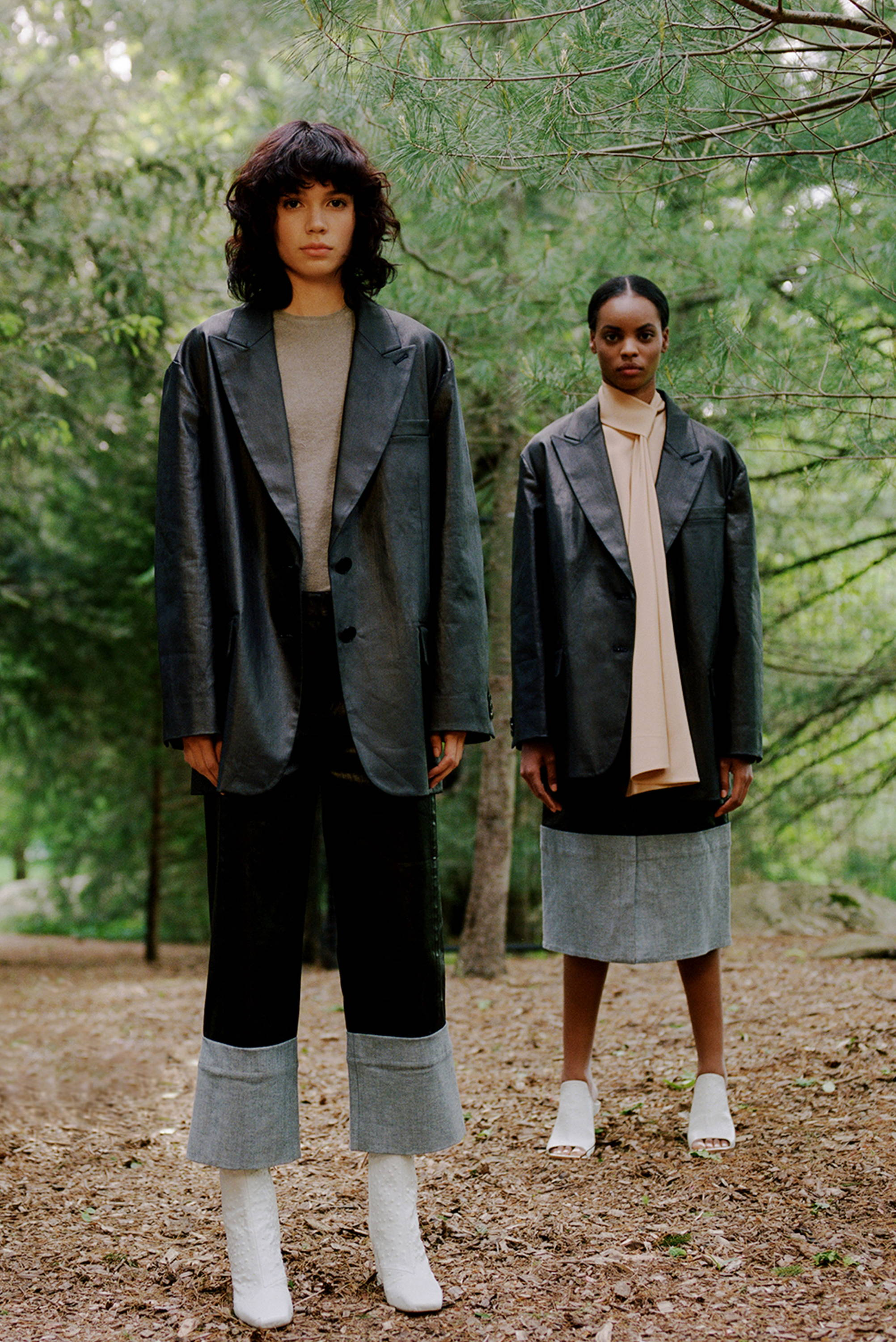 Two models wearing coated black denim and white shoes.