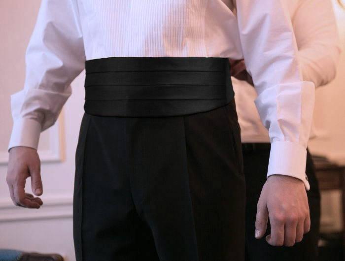 Man getting help putting on a cummerbund in formal attire