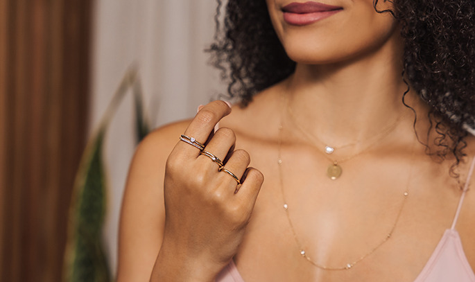 woman displaying stacked rings on her hand including rings that are accented, solid and with a center stone