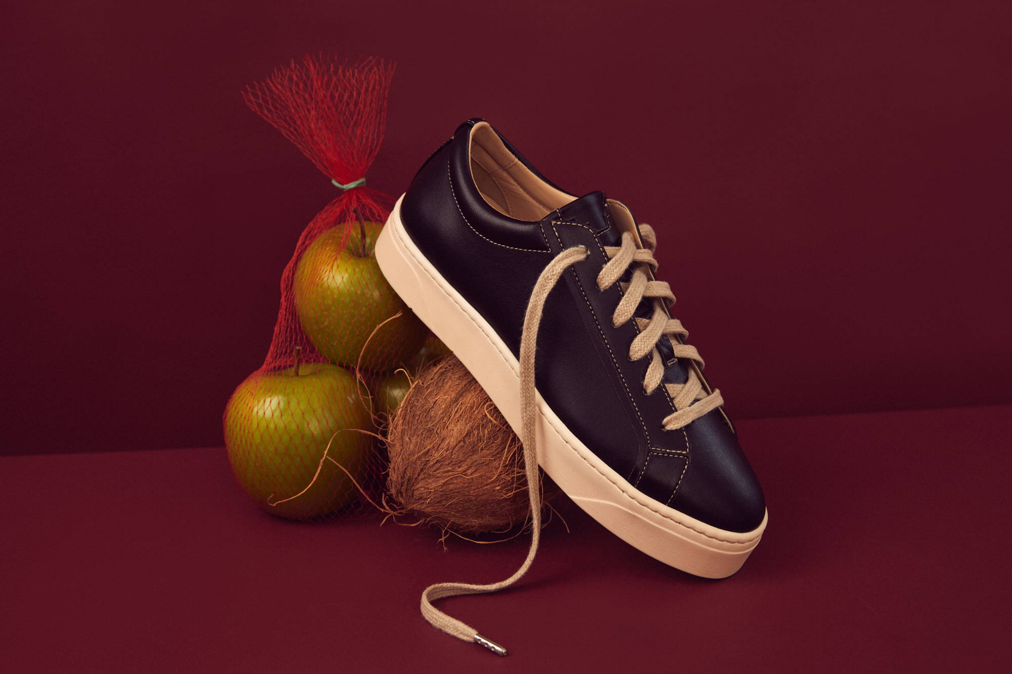 Plant-based luxury footwear - our Mel vegan apple and coconut sneaker pictured on a dark red background alongside apples and coconuts