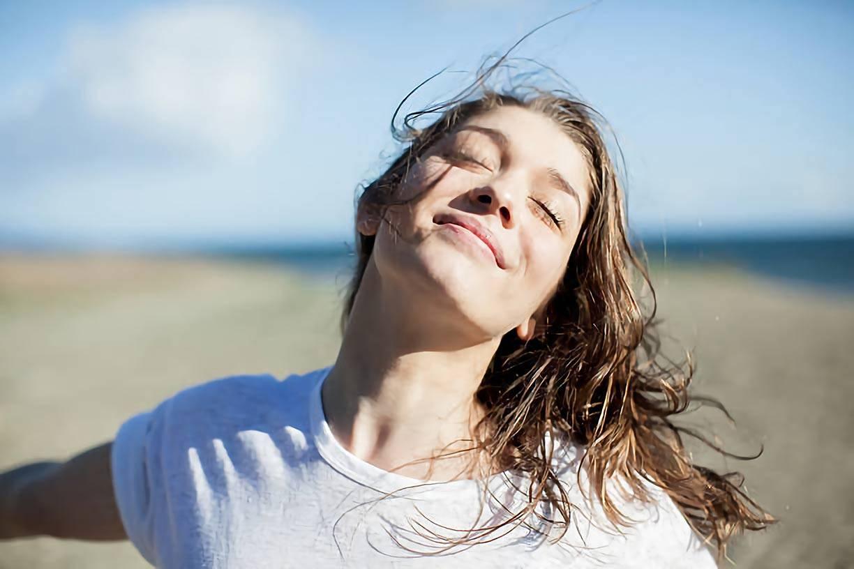 woman enjoying the sunlight at a beach