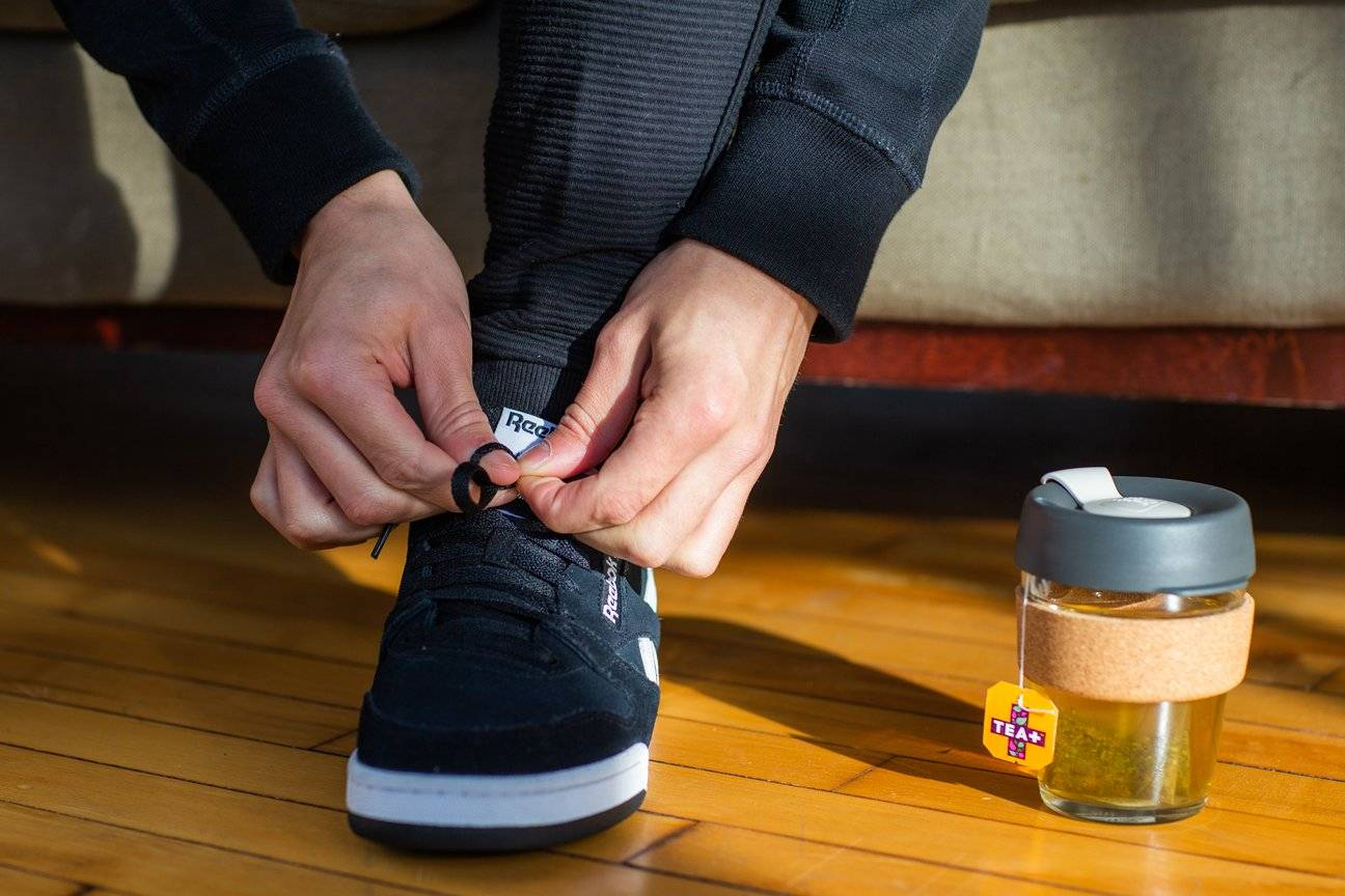 Man Tying Shoe Lace Next To Vitamin Tea