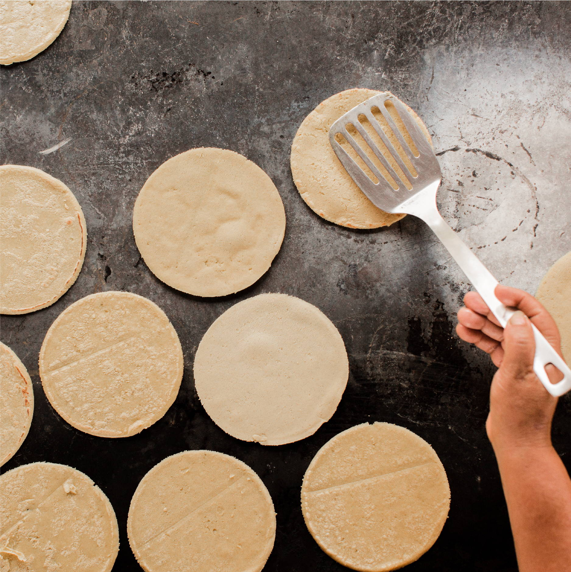 Fresh corn tortillas are cooked on a wood-fired cast iron skillet and being flipped by a spatula.