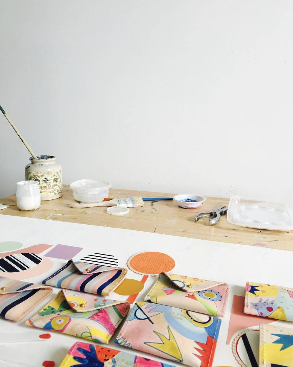Artist's studio with paint and brushes and hand painted leather wallets in the foreground.