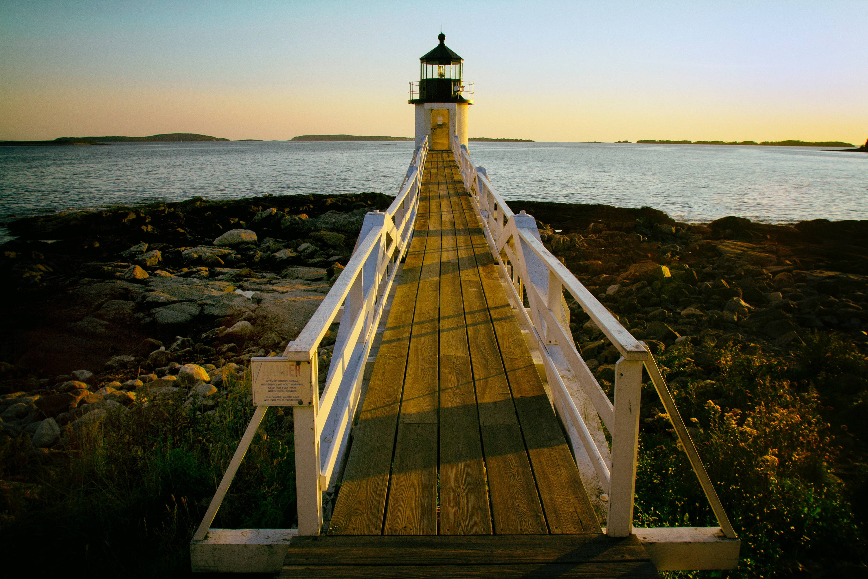 Maine State Parks: Secluded Beaches in Maine. Long dock with white handrails on either side leads to lighthouse on the water.