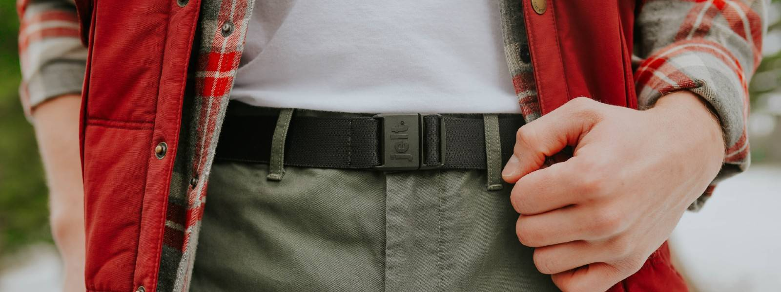 Man wearing JeltX Adjustable belt in black, with red vest, flannel and khaki pants.