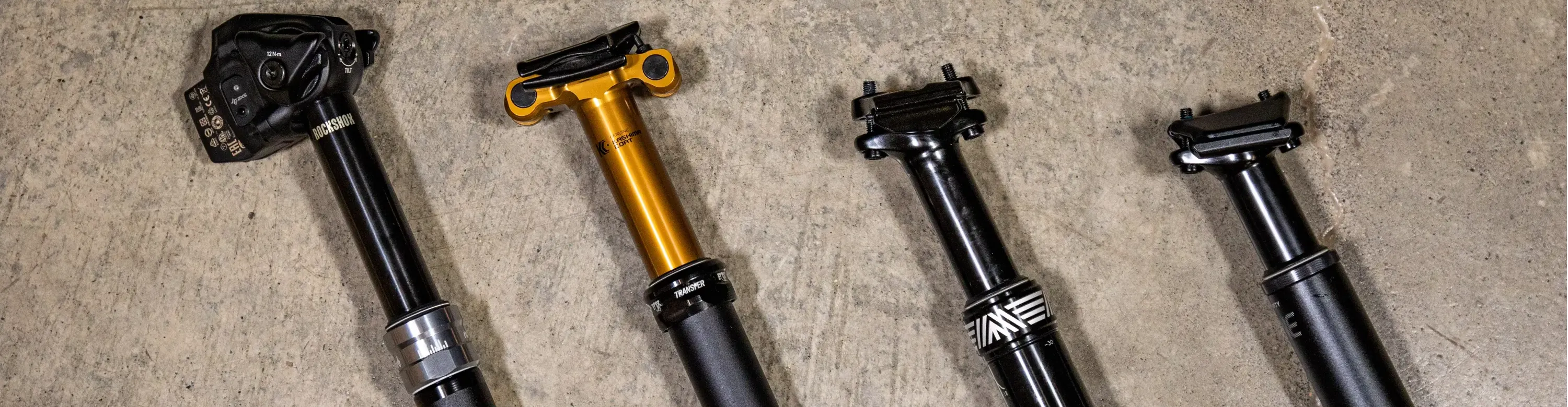 MTB Dropper Seatpost collection Image RockShox Reverb AXS Fox Transfer Post Factory Series PNW Components Rainier Gen 3 OneUp Components Dropper V2 laying down on the ground