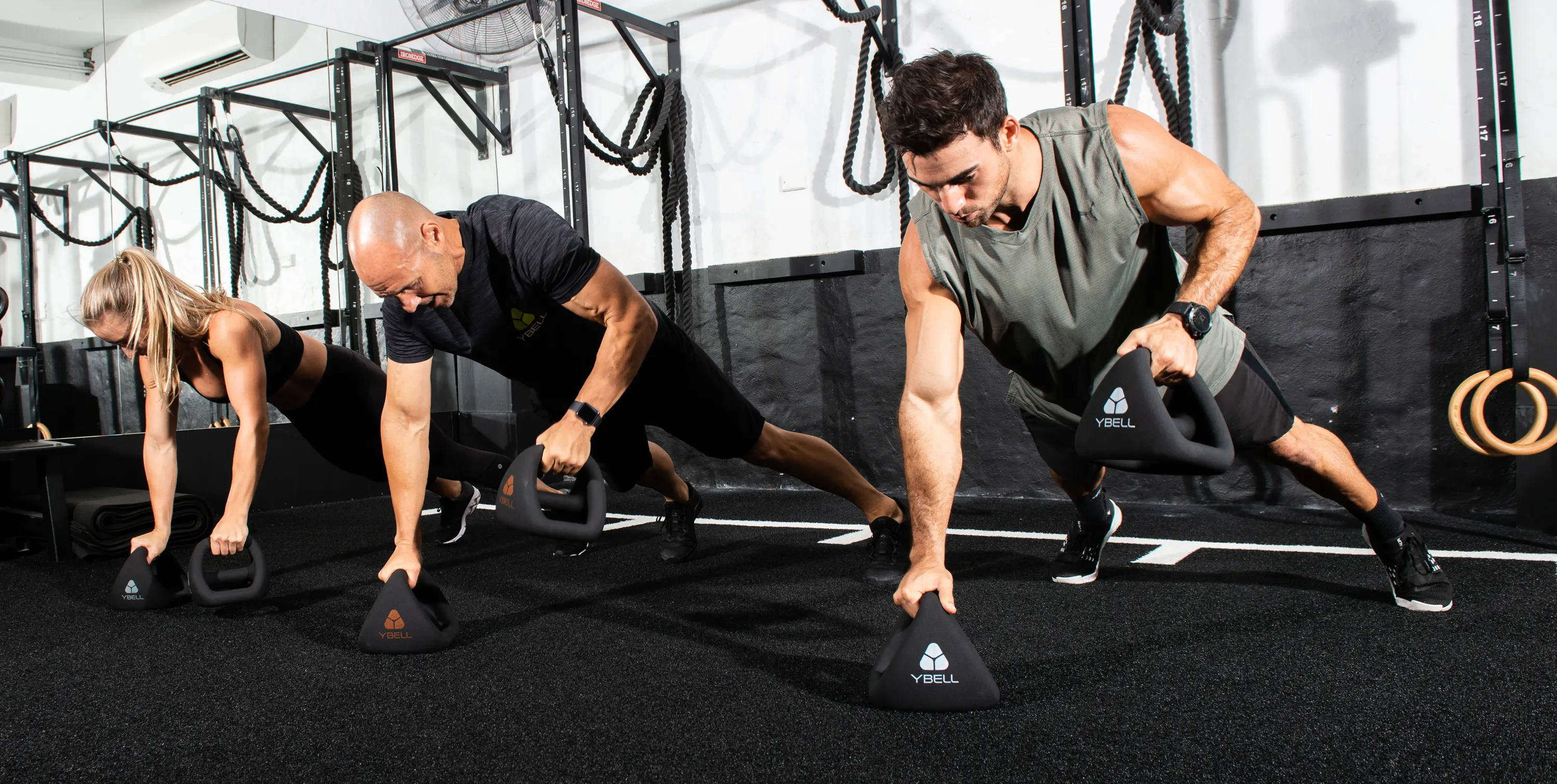 Athletes training with YBells as push-up stands in a gym