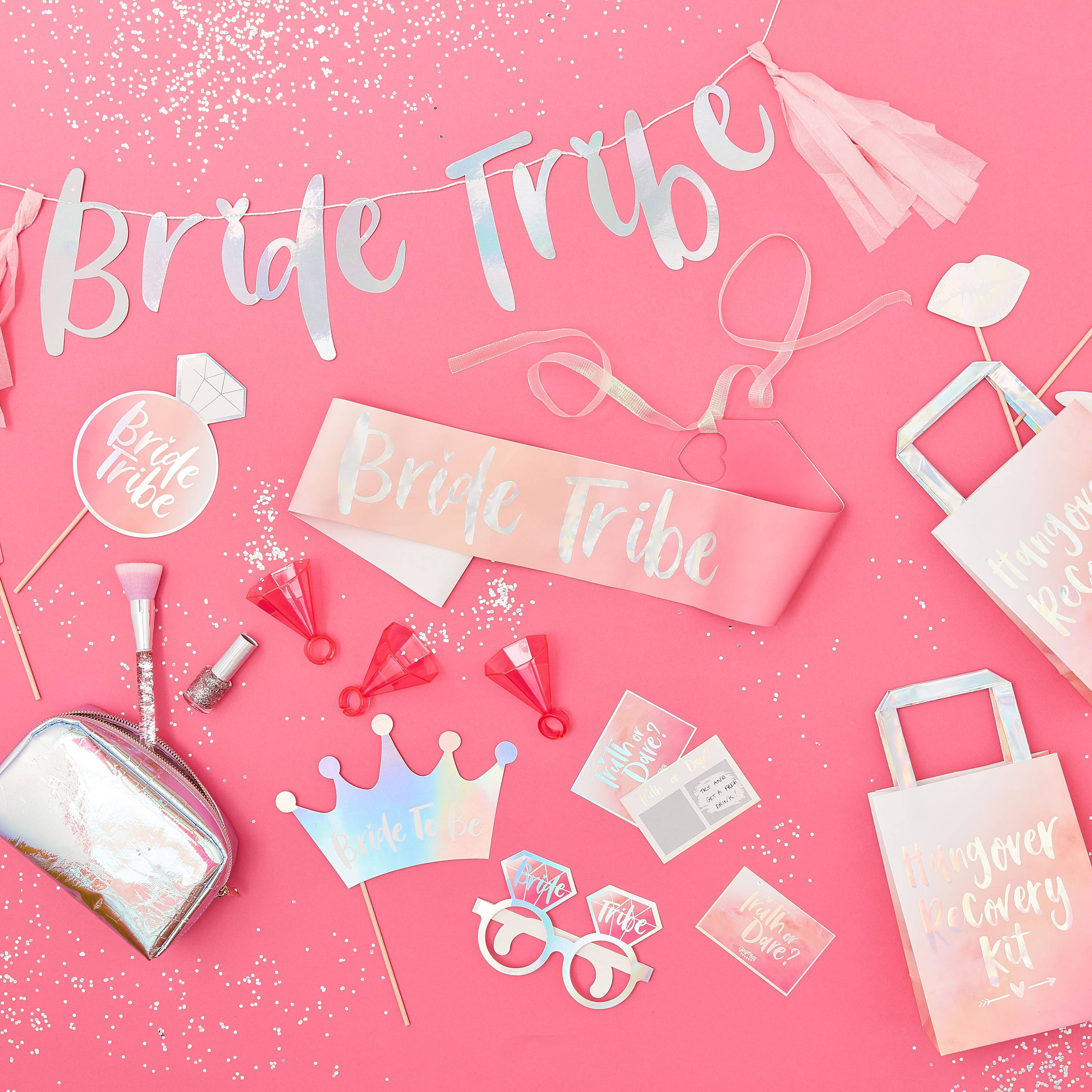A photo of a colourful pink table topped with hen party decorations including a hen party sash saying 'Bride Tribe', truth or dare scatchcards, hen party photo booth props and gift bags too, all with a hen party banner above it saying Bride Tribe