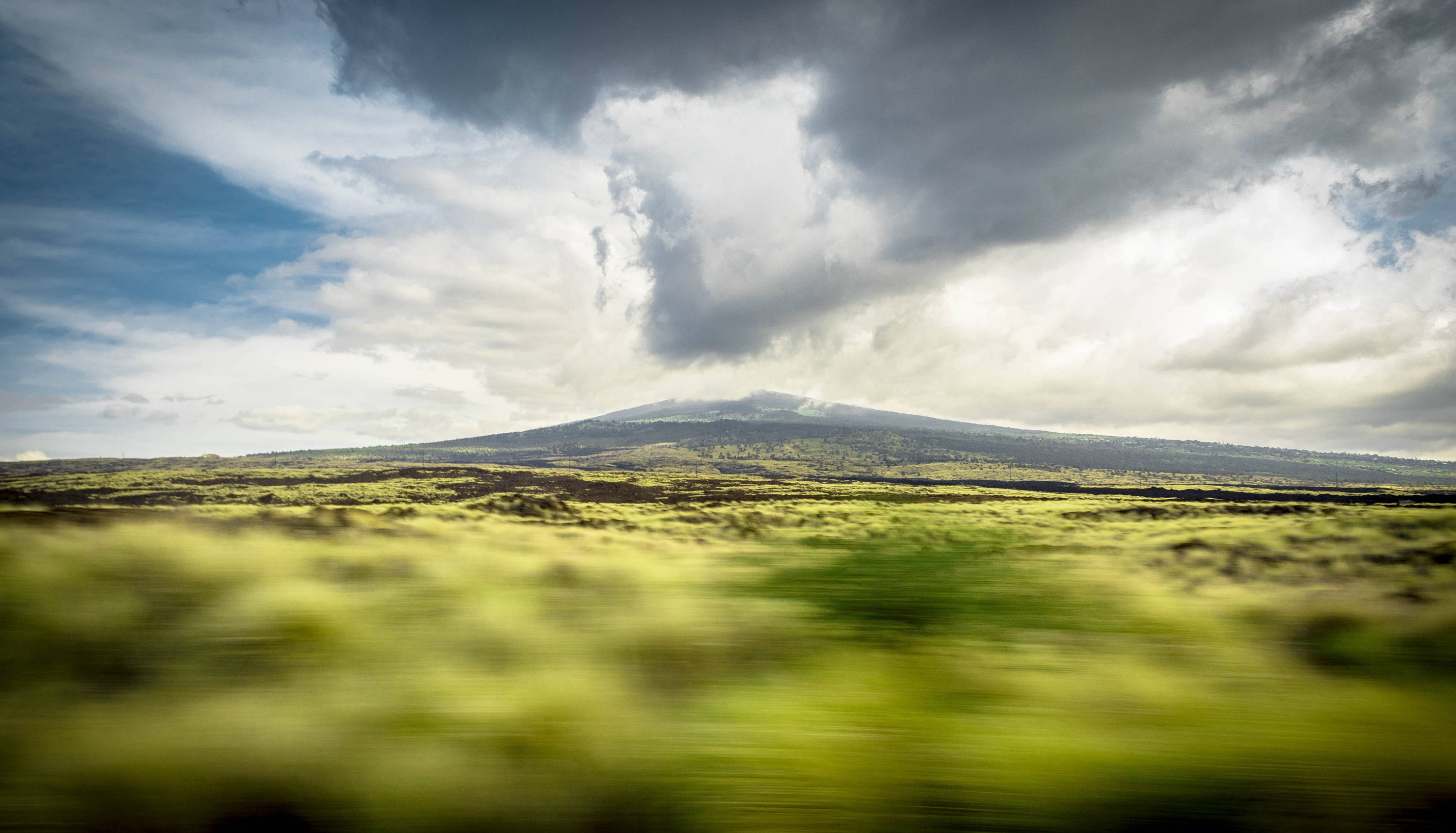 Things to Do in Hilo, Hawaii: Clouds loom over mountain in the distance with green space below; things to do in Hilo, Hawaii.