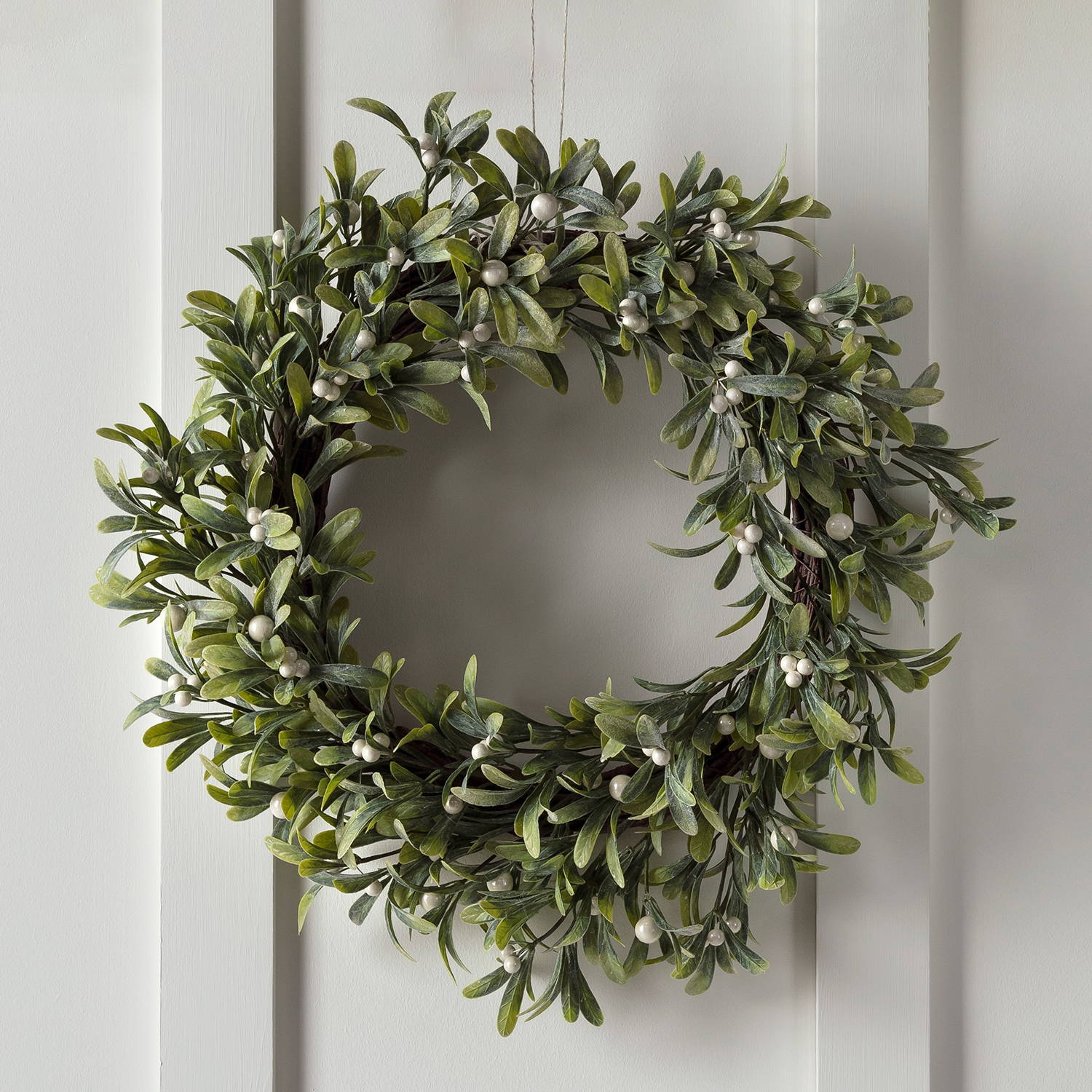 green leaf mistletoe Christmas wreath hung up on white background