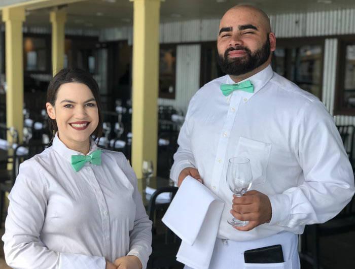 Waiters wearing white dress shirts and seafoam bow ties
