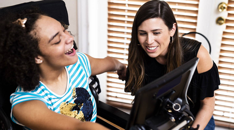 Junge Frau benutzt ein Gerät der I-Serie von Tobii Dynavox mit ihrer Betreuerin