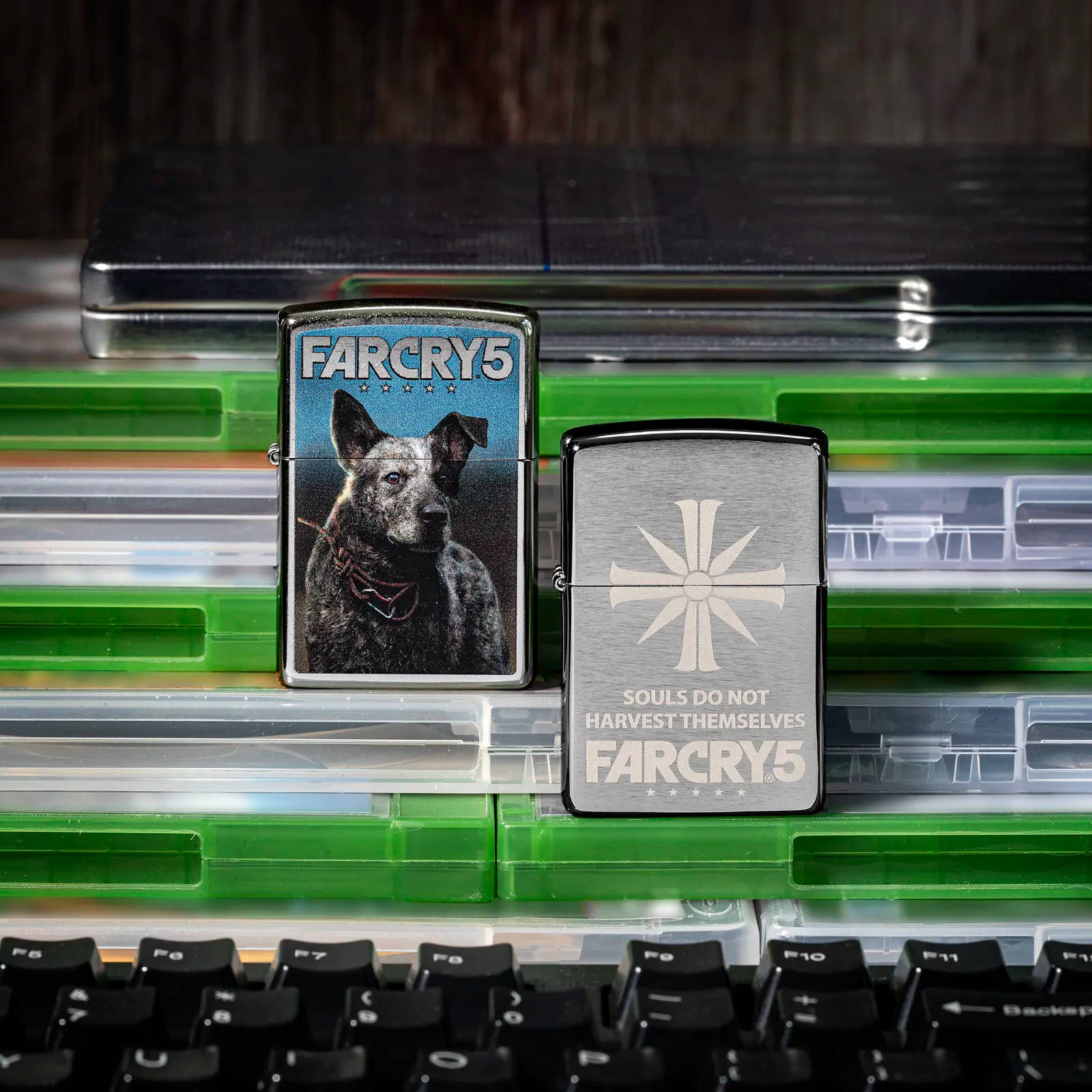 Far Cry 5 lighters standing on game cases with a keyboard in the foreground