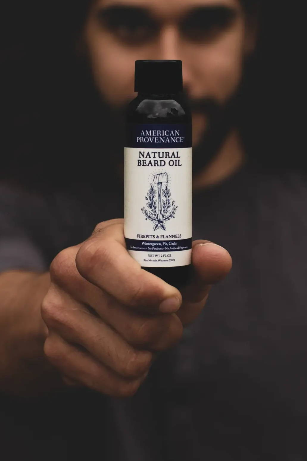 man holding beard oil bottle