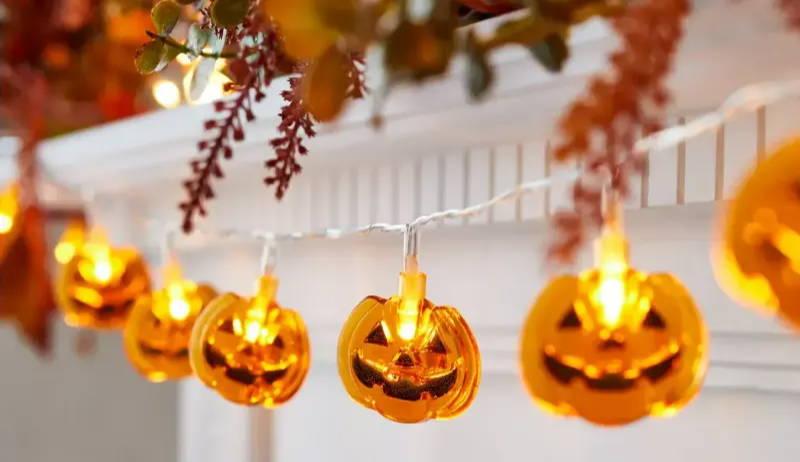 Illuminated Halloween pumpkin fairy lights draped along mantel