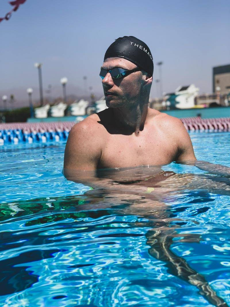Man in the pool with custom goggles and TheMagic5 swim cap on