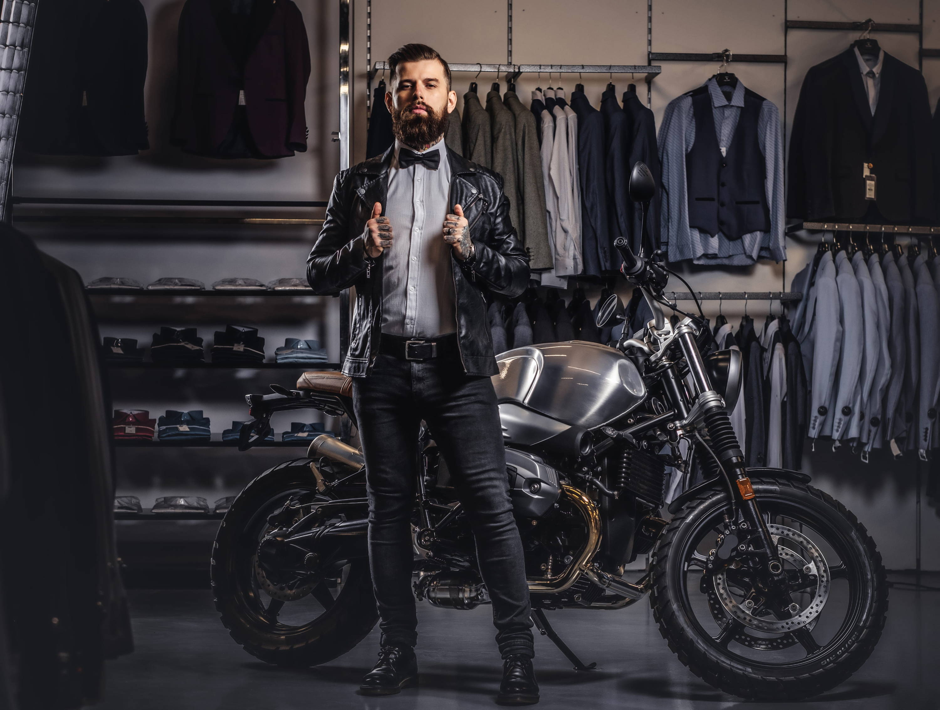 Rugged rebel mens style, man poses in front of motorbike in leather jacket and bowtie