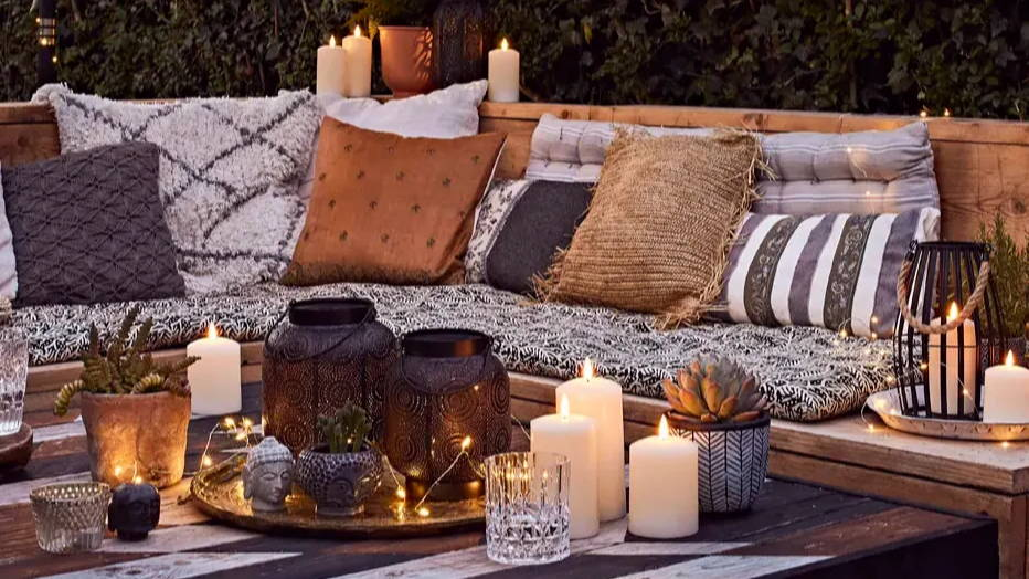 Outdoor TruGlow candles and lanterns styled on garden table with micro lights