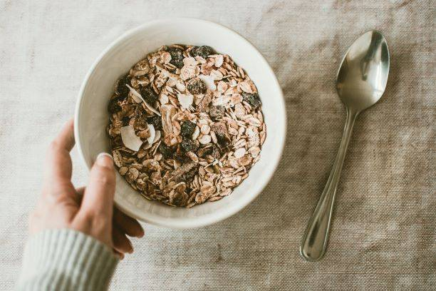 Person Holding Bowl Full Of Oats And Raisins