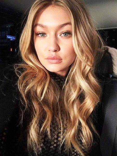 Gigi Hadid with curly hair and subtle layers