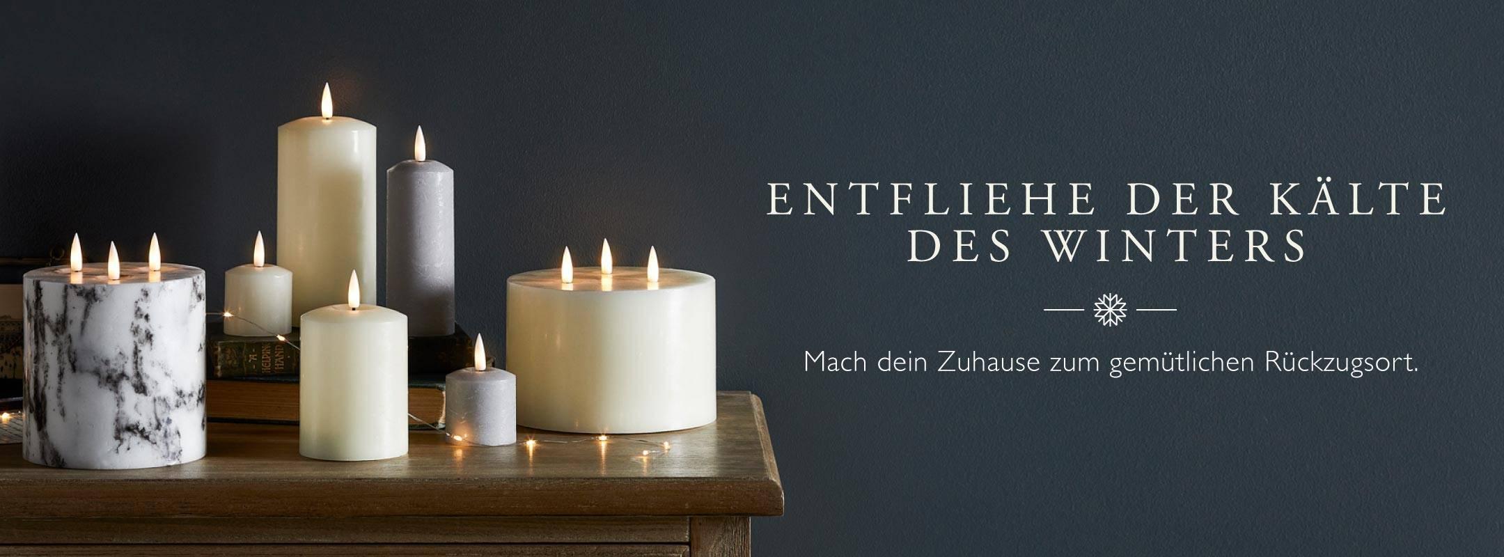 Verschiedene TruGlow LED Kerzen in Elfenbein und Grau arrangiert auf einem Holztisch