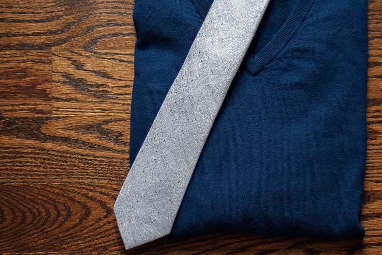 Gray textured tie on navy sweater