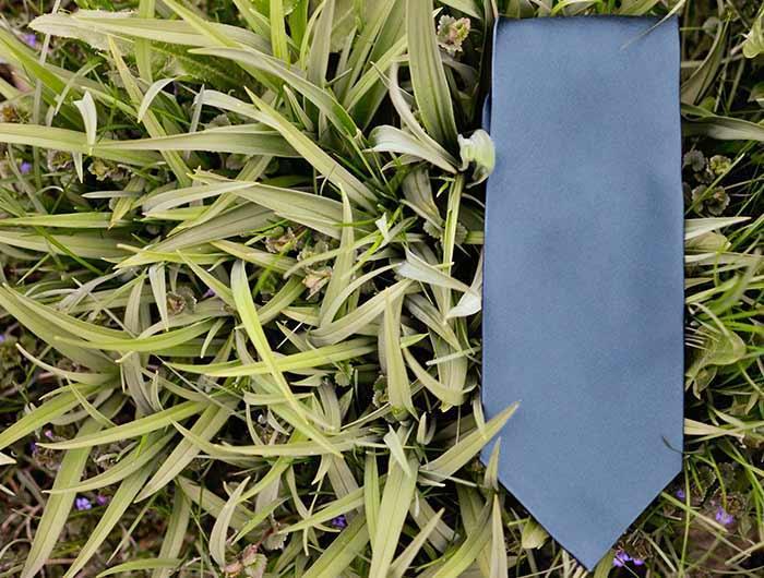 Dusty blue necktie, solid, in grass