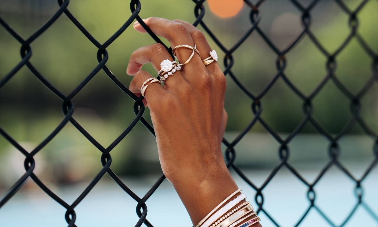 Close up of model wearing Ring Concierge rings holding a fence