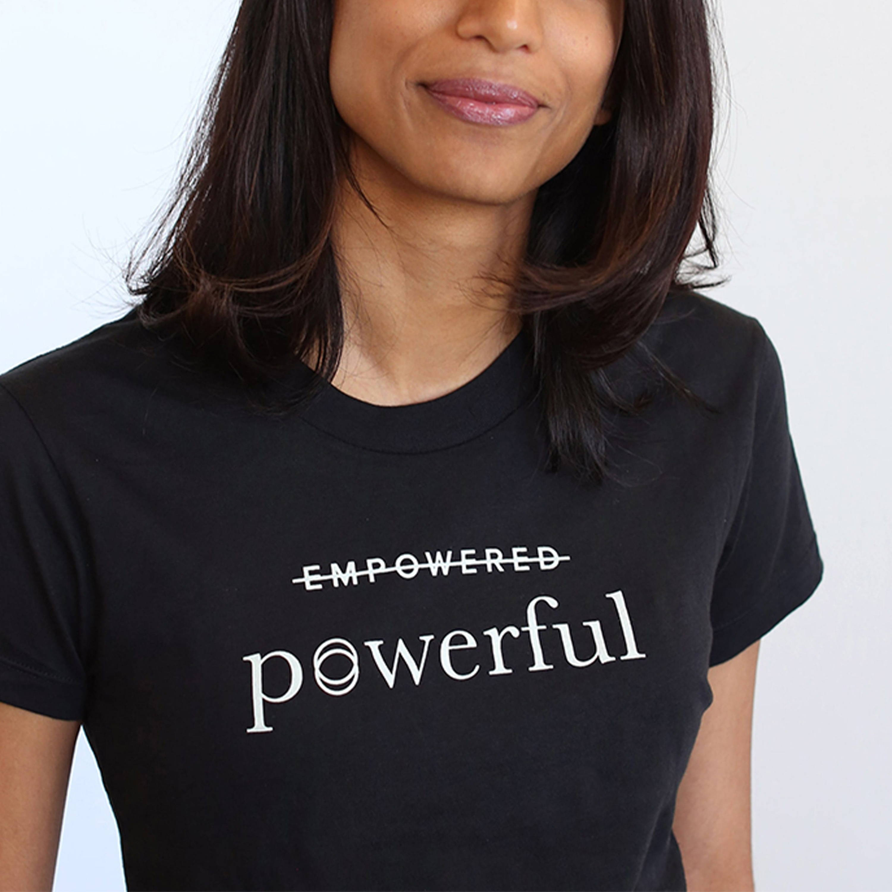 "A black t-shirt that features the word ""empowered"" with a strikethrough line and the word ""powerful"" written underneath"