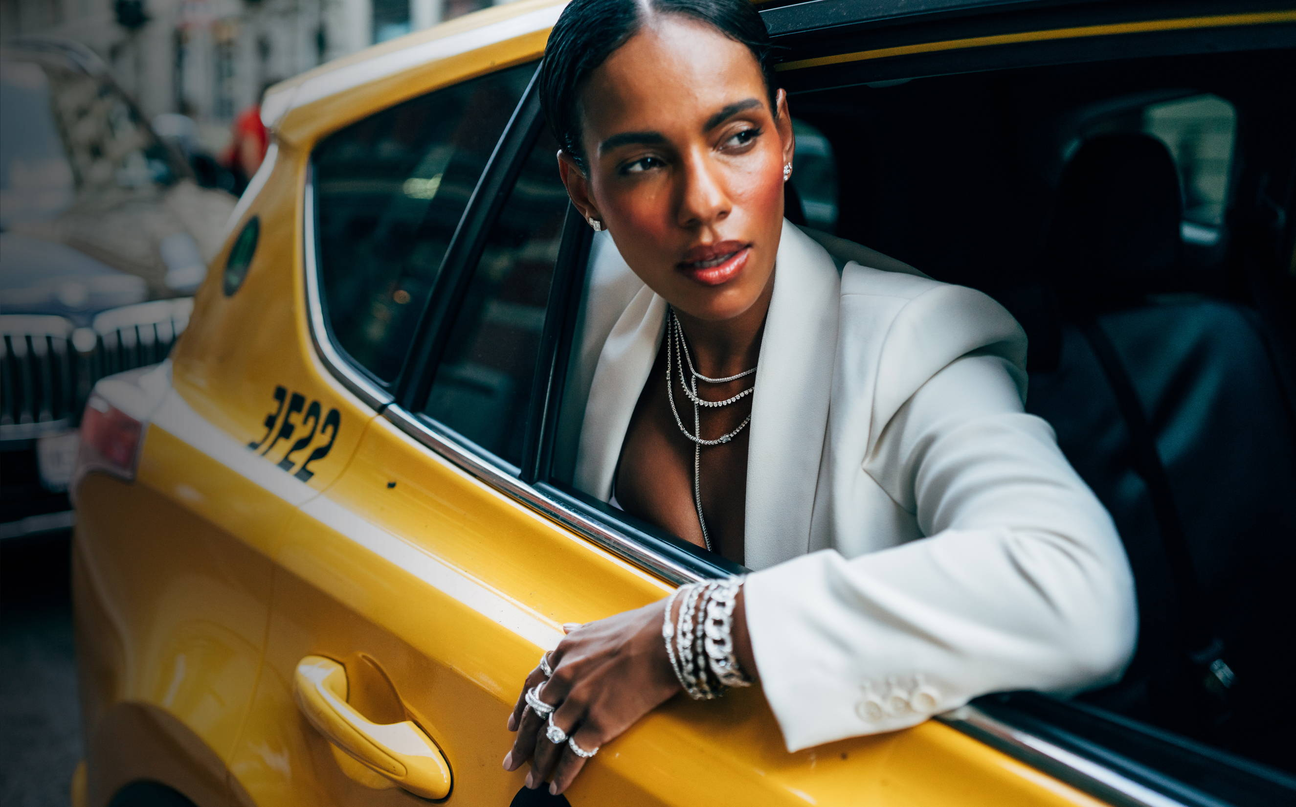 Model wearing Ring Concierge jewelry leaning out the window of a NYC taxi