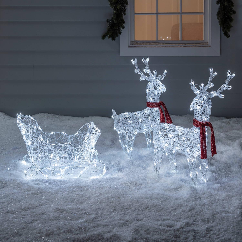 Zwei weiße LED-Rentiere mit Schlitten und Schals.